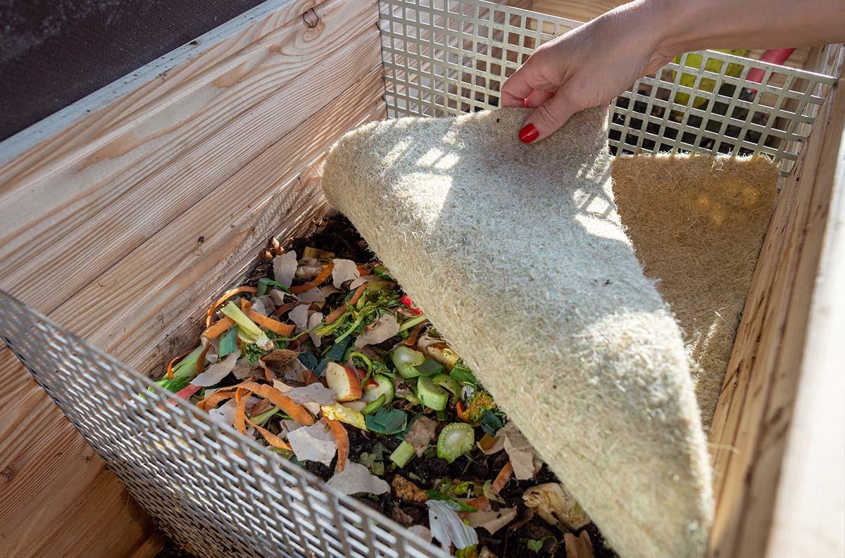 Wurmkomposter gefüllt mit Bioabfall und Humus, bedeckt mit einer Hanfmatte